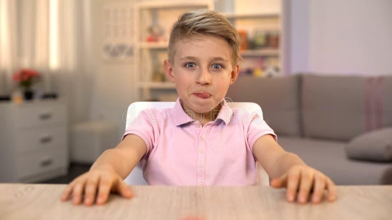Ευτυχές αγόρι που γλείφει τα χείλια και που εξετάζει τα νόστιμα τρόφιμα στον πίνακα κουζινών, διατροφή στοκ φωτογραφίες με δικαίωμα ελεύθερης χρήσης