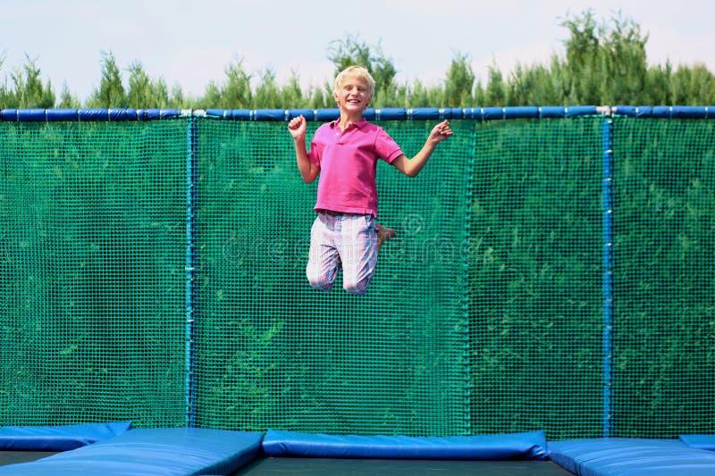 Ευτυχές αγόρι που πηδά στο τραμπολίνο στοκ φωτογραφία με δικαίωμα ελεύθερης χρήσης