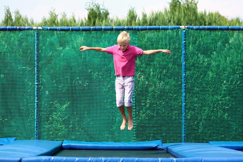 Ευτυχές αγόρι που πηδά στο τραμπολίνο στοκ εικόνες με δικαίωμα ελεύθερης χρήσης