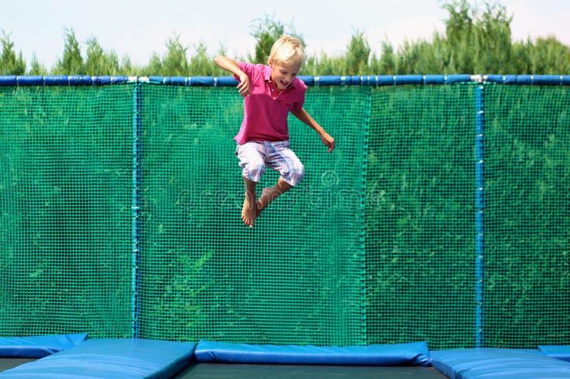 Ευτυχές αγόρι που πηδά στο τραμπολίνο στοκ εικόνα με δικαίωμα ελεύθερης χρήσης