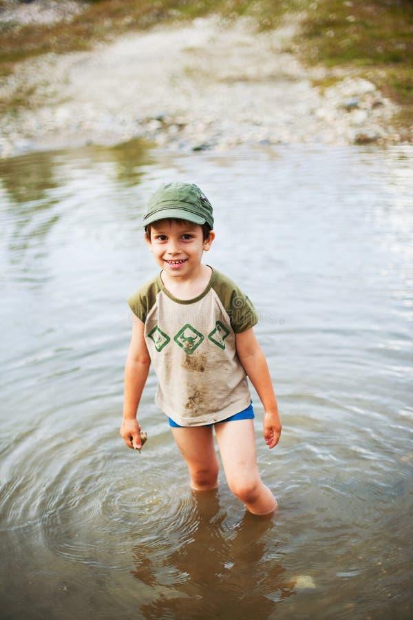 Ευτυχές αγόρι που στέκεται στη λίμνη στοκ εικόνες