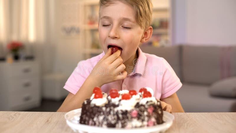 Ευτυχές αγόρι που τρώει το κεράσι από την κορυφή του κέικ κρέμας, γλυκό επιδόρπιο, πρόχειρο φαγητό παιδικής ηλικίας στοκ εικόνα