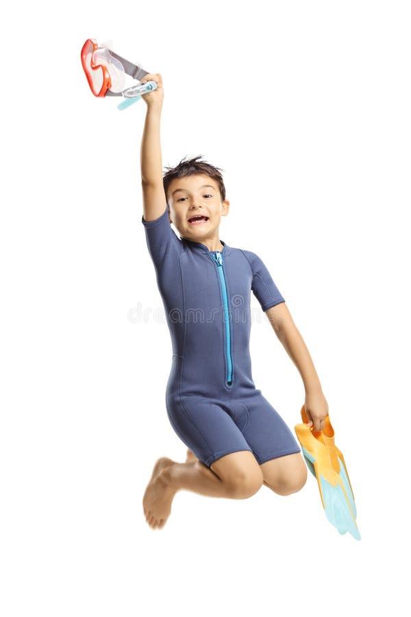 Ευτυχές αγόρι πτερύγια και το άλμα μιας wetsuit εκμετάλλευσης στα swmming στοκ εικόνες