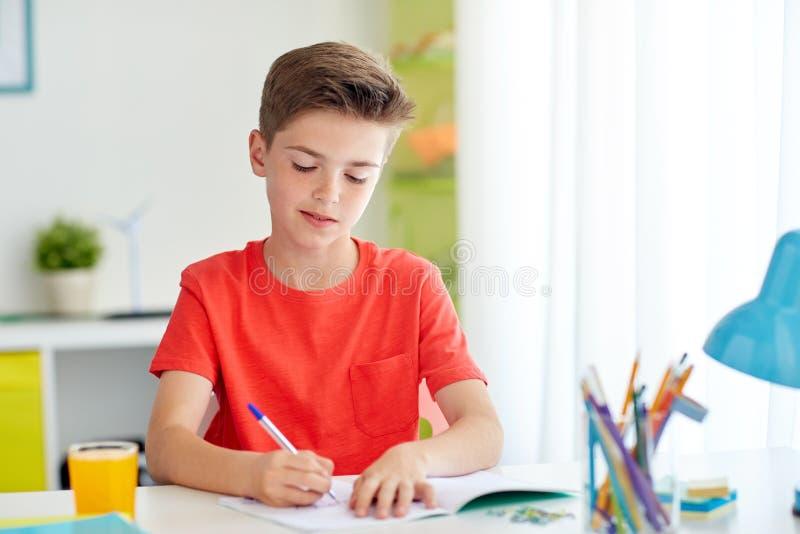 Ευτυχές αγόρι σπουδαστών που γράφει στο σημειωματάριο στο σπίτι στοκ φωτογραφία με δικαίωμα ελεύθερης χρήσης