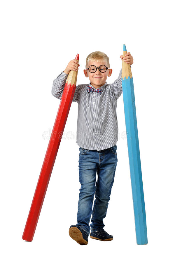 Ευτυχές αγόρι στα γυαλιά και bowtie τοποθέτηση με ένα τεράστιο μολύβι έννοια εκπαιδευτική Απομονωμένος πέρα από το λευκό στοκ φωτογραφίες