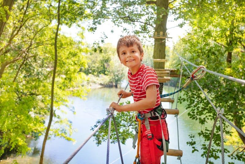 Ευτυχές αγόρι στη γέφυρα σχοινιών δέντρων στο πάρκο περιπέτειας στοκ φωτογραφία με δικαίωμα ελεύθερης χρήσης