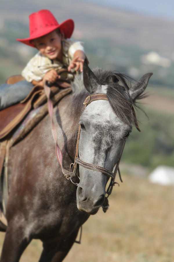 Ευτυχές αγόρι στο άλογο οδήγησης καπέλων κάουμποϋ υπαίθρια στοκ φωτογραφίες με δικαίωμα ελεύθερης χρήσης