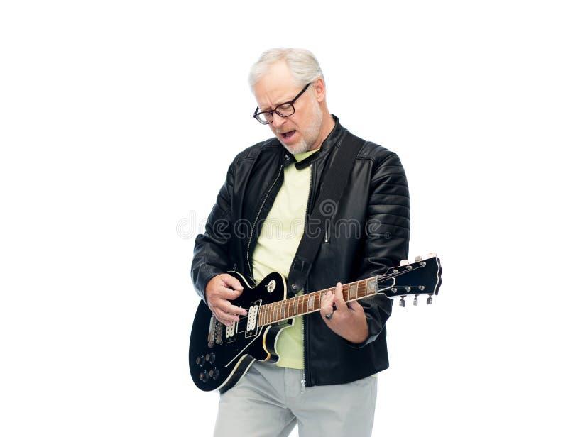 Ευτυχές ανώτερο άτομο που παίζει την ηλεκτρική κιθάρα στοκ εικόνες