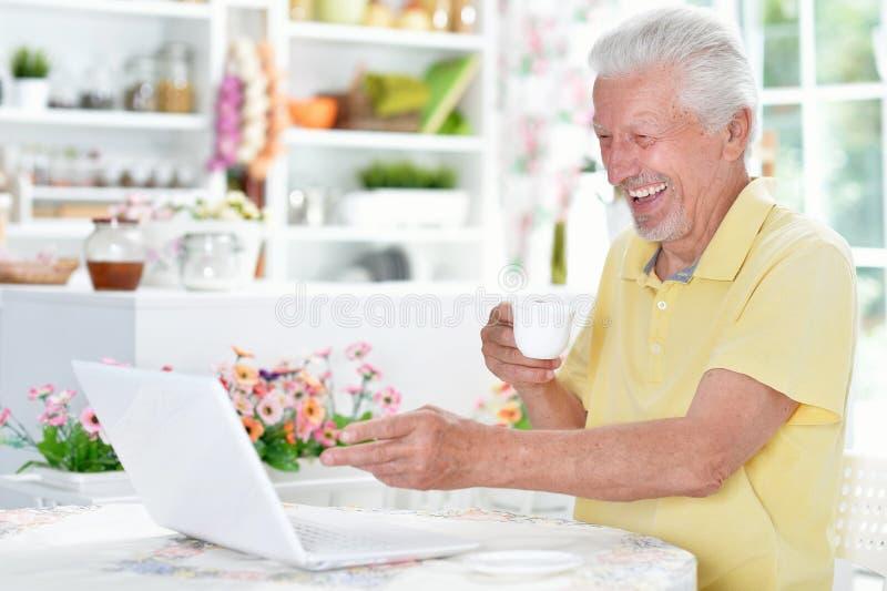 Ευτυχές ανώτερο άτομο που χρησιμοποιεί το lap-top πίνοντας το τσάι στοκ φωτογραφία με δικαίωμα ελεύθερης χρήσης