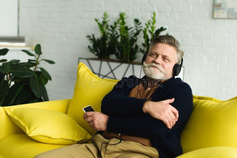 ευτυχές ανώτερο άτομο στη μουσική ακούσματος ακουστικών με το smartphone στοκ εικόνες με δικαίωμα ελεύθερης χρήσης