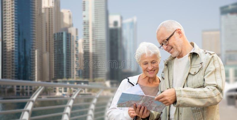 Ευτυχές ανώτερο ζεύγος με το χάρτη πέρα από την πόλη του Ντουμπάι στοκ εικόνα