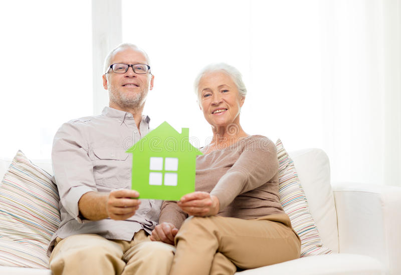 Ευτυχές ανώτερο ζεύγος που αγκαλιάζει στον καναπέ στο σπίτι στοκ εικόνες