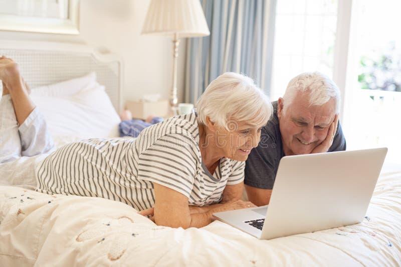 Ευτυχές ανώτερο ζεύγος που βρίσκεται στο κρεβάτι τους που χρησιμοποιεί ένα lap-top στοκ εικόνες