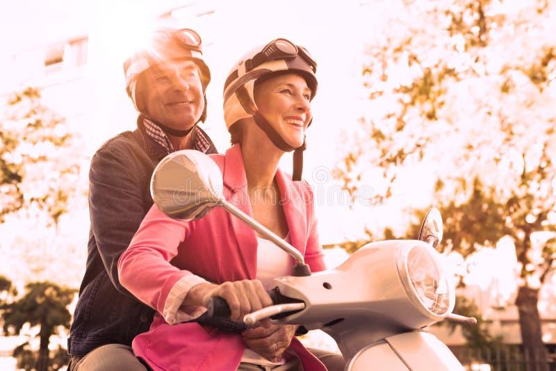 Ευτυχές ανώτερο ζεύγος που οδηγά ένα μοτοποδήλατο απεικόνιση αποθεμάτων