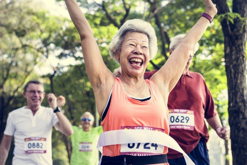 Ευτυχές ανώτερο τρέξιμο μέσω της γραμμής τερματισμού στοκ φωτογραφία