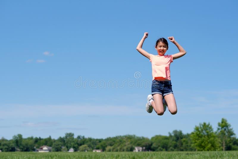 Ευτυχές ασιατικό άλμα κοριτσιών εφήβων υψηλό στον αέρα στοκ φωτογραφία