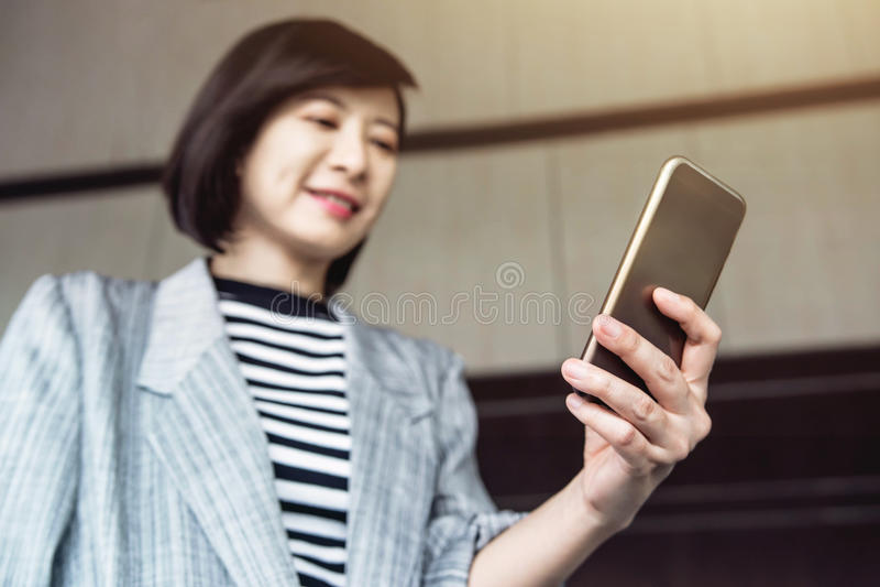 Ευτυχές ασιατικό έξυπνο τηλέφωνο χρήσης εργαζόμενων γυναικών στοκ φωτογραφίες