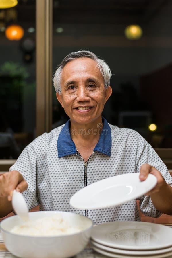 Ευτυχές ασιατικό αρσενικό ανώτερο εξυπηρετώντας ρύζι στοκ φωτογραφίες