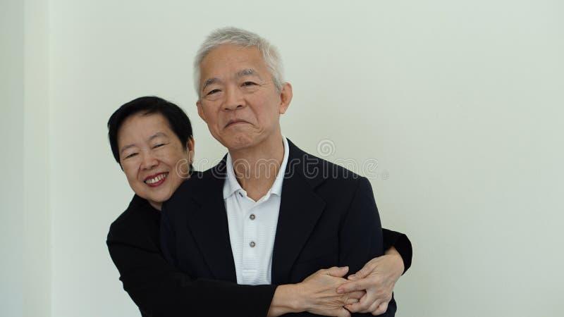 Ευτυχές ασιατικό ηλικιωμένο ζεύγος χαμόγελου στην επιχειρησιακή ενδυμασία, ιδιοκτήτης ΜΜΕ στοκ φωτογραφία με δικαίωμα ελεύθερης χρήσης