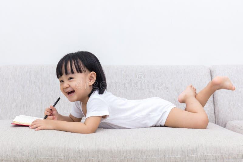 Ευτυχές ασιατικό κινεζικό μικρό κορίτσι που βάζει στο βιβλίο γραψίματος καναπέδων στοκ φωτογραφία με δικαίωμα ελεύθερης χρήσης