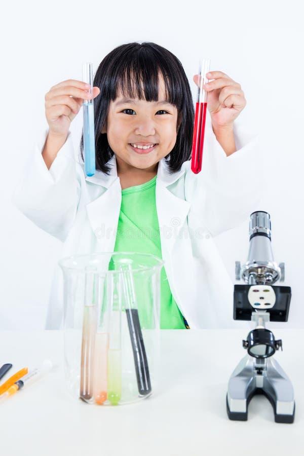 Ευτυχές ασιατικό κινεζικό μικρό κορίτσι που εξετάζει το σωλήνα δοκιμής με ομοιόμορφο στοκ εικόνα με δικαίωμα ελεύθερης χρήσης