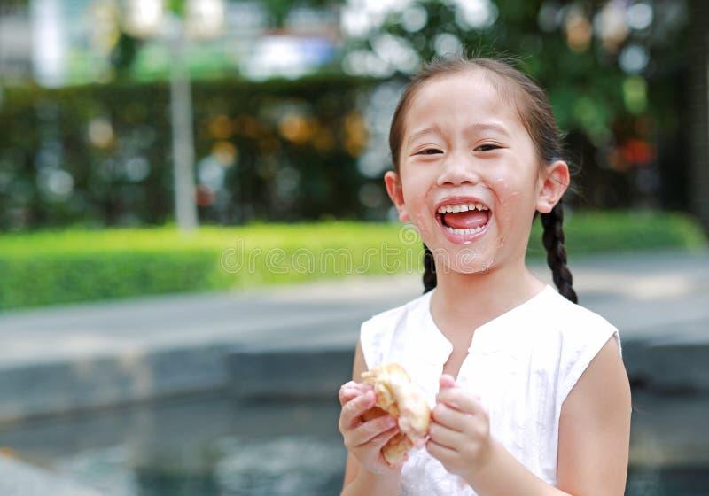Ευτυχές ασιατικό μικρό κορίτσι που τρώει το ψωμί με το γεμισμένο φράουλα-γεμισμένο επιδόρπιο και λεκιασμένος γύρω από το στόμα τη στοκ φωτογραφία