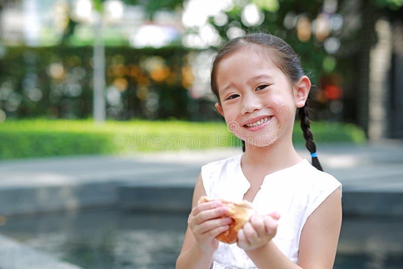 Ευτυχές ασιατικό μικρό κορίτσι που τρώει το ψωμί με το γεμισμένο φράουλα-γεμισμένο επιδόρπιο και λεκιασμένος γύρω από το στόμα τη στοκ εικόνες με δικαίωμα ελεύθερης χρήσης