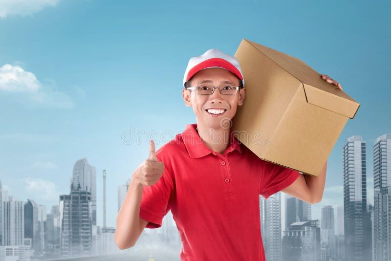Ευτυχές ασιατικό φέρνοντας κουτί από χαρτόνι ατόμων αγγελιαφόρων στον ώμο στοκ φωτογραφία με δικαίωμα ελεύθερης χρήσης