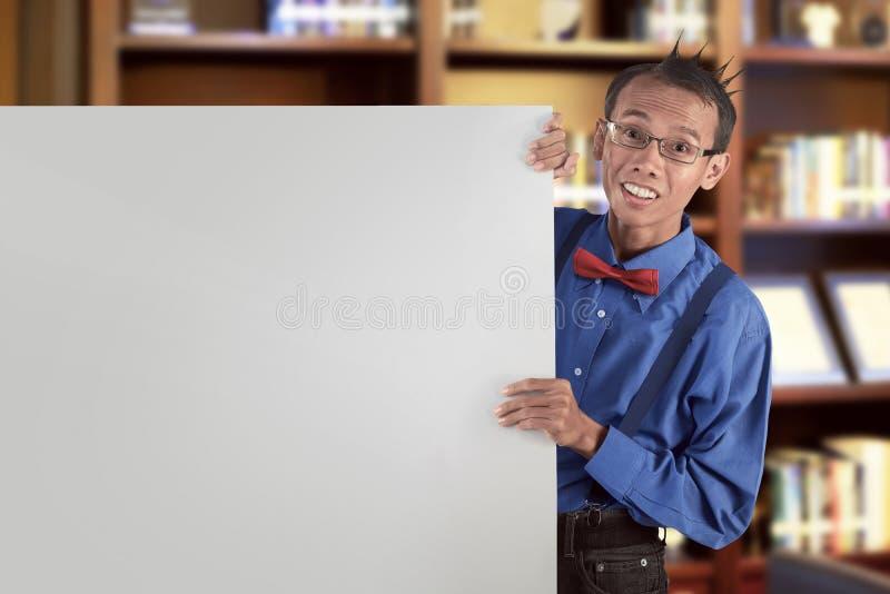 Ευτυχές ασιατικό nerdy άτομο που παρουσιάζει κενό λευκό πίνακα για το copyspace στοκ εικόνες με δικαίωμα ελεύθερης χρήσης