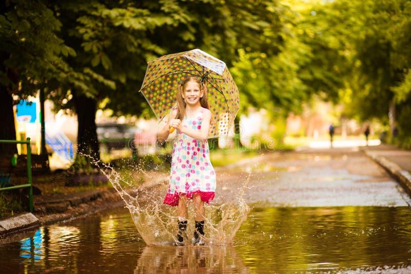 Ευτυχές αστείο κορίτσι παιδιών με την ομπρέλα που πηδά στις λακκούβες στις λαστιχένιες μπότες και το γέλιο στοκ εικόνες