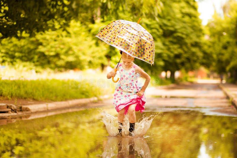 Ευτυχές αστείο κορίτσι παιδιών με την ομπρέλα που πηδά στις λακκούβες στις λαστιχένιες μπότες και το γέλιο στοκ φωτογραφίες με δικαίωμα ελεύθερης χρήσης