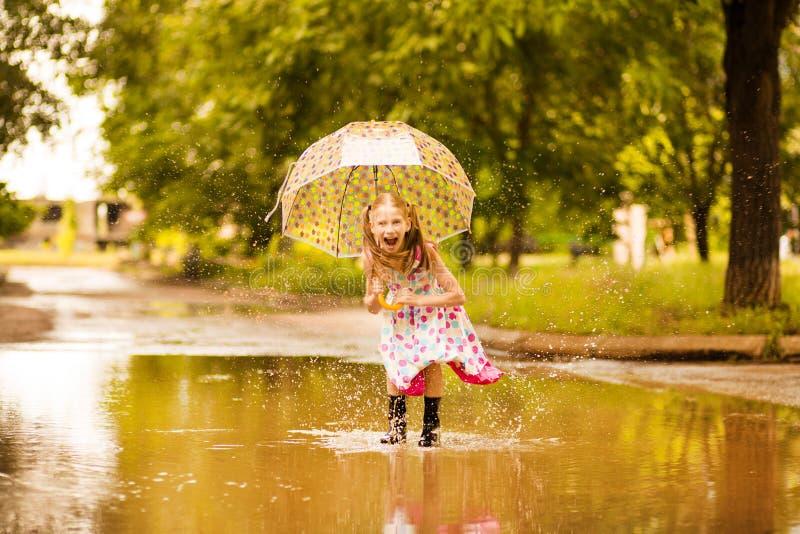 Ευτυχές αστείο κορίτσι παιδιών με την ομπρέλα που πηδά στις λακκούβες στις λαστιχένιες μπότες και το γέλιο στοκ φωτογραφίες