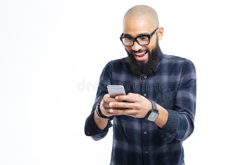 Ευτυχές αφρικανικό άτομο με τη γενειάδα που χαμογελά και που χρησιμοποιεί το κινητό τηλέφωνο στοκ φωτογραφίες με δικαίωμα ελεύθερης χρήσης