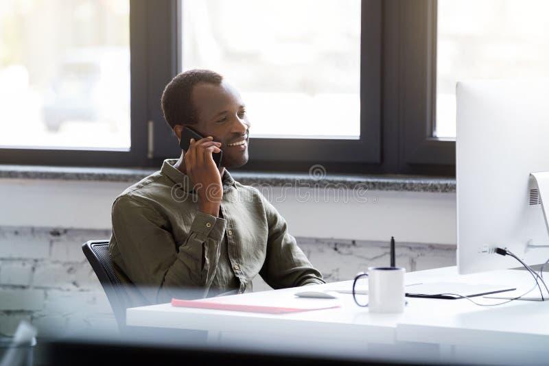 Ευτυχές αφρικανικό άτομο που μιλά στο κινητό τηλέφωνό του στοκ φωτογραφίες
