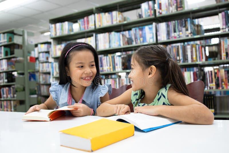 Ευτυχές βιβλίο ανάγνωσης σχολικών κοριτσιών ζευγών στη βιβλιοθήκη στοκ φωτογραφίες με δικαίωμα ελεύθερης χρήσης