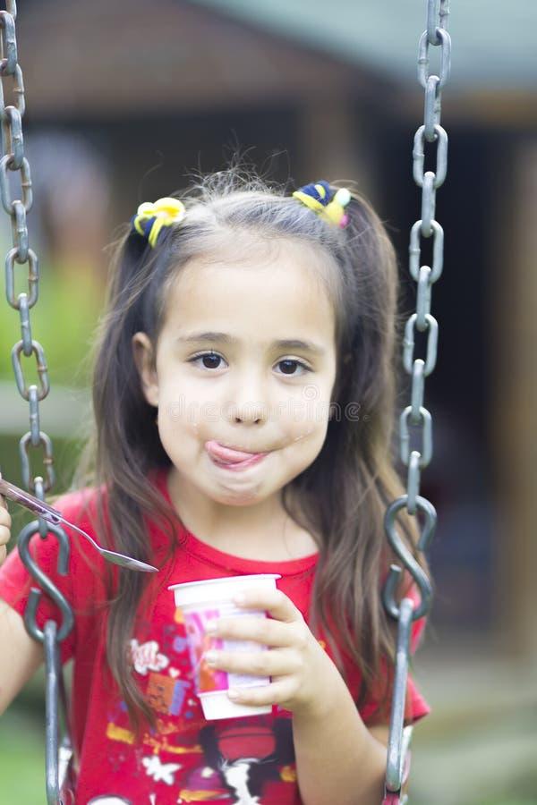 Ευτυχές γάλα ή γιαούρτι κοριτσιών πόσιμο στοκ εικόνα με δικαίωμα ελεύθερης χρήσης
