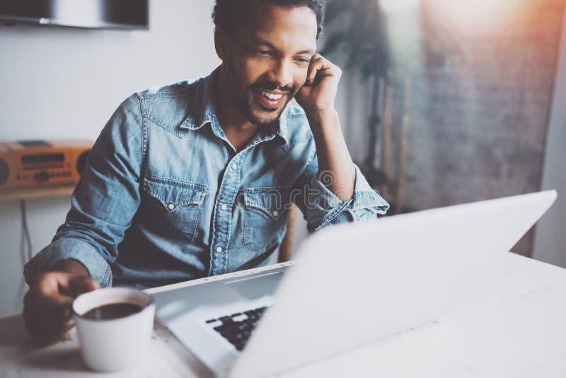 Ευτυχές γενειοφόρο αφρικανικό άτομο που κάνει την τηλεοπτική συνομιλία μέσω του σύγχρονου lap-top με τους συνεργάτες κρατώντας το στοκ εικόνες