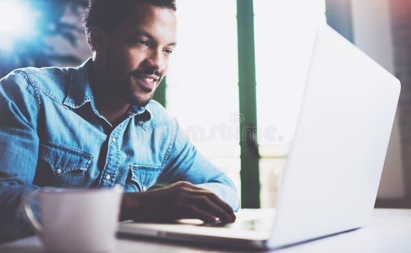 Ευτυχές γενειοφόρο αφρικανικό άτομο που χρησιμοποιεί το lap-top στο σπίτι καθμένος τον ξύλινο πίνακα Ο τύπος δακτυλογραφεί στο πλ στοκ φωτογραφίες