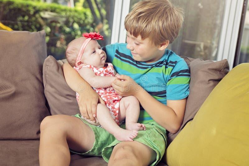 Ευτυχές γελώντας αγόρι που κρατά τη νεογέννητη αδελφή μωρών ύπνου του στοκ φωτογραφία με δικαίωμα ελεύθερης χρήσης