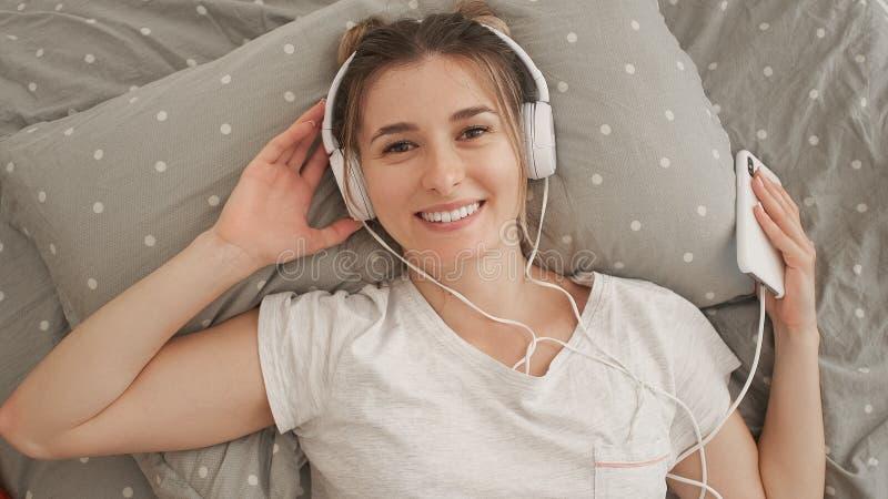 Ευτυχές γυναίκα ή έφηβη στα ακουστικά που ακούει τη μουσική από το smartphone στοκ φωτογραφία με δικαίωμα ελεύθερης χρήσης