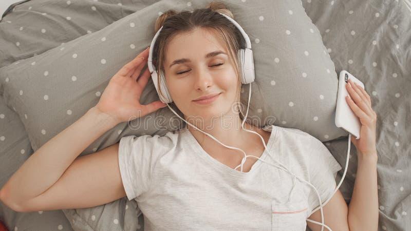 Ευτυχές γυναίκα ή έφηβη στα ακουστικά που ακούει τη μουσική από το smartphone στοκ εικόνες