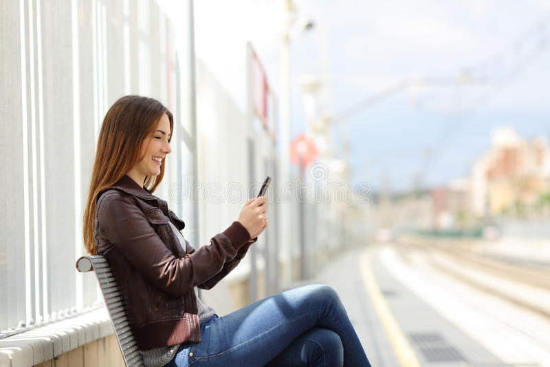 Ευτυχές γυναικών σε ένα έξυπνο τηλέφωνο σε έναν σταθμό τρένου στοκ εικόνα