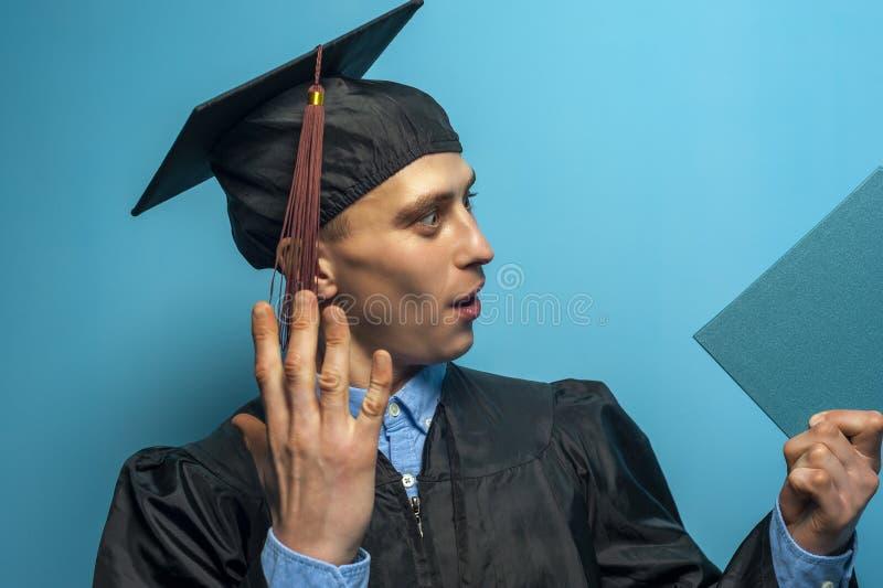 Ευτυχές διαβαθμισμένο άτομο που κρατά ψηλά ένα δίπλωμα στοκ εικόνα