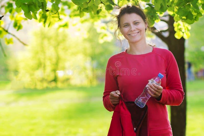 Ευτυχές ελκυστικό κορίτσι brunette με το μπουκάλι νερό και σακίδιο πλάτης στο πράσινο πάρκο πόλεων πρίν εκπαιδεύει την ικανότητα στοκ εικόνα με δικαίωμα ελεύθερης χρήσης