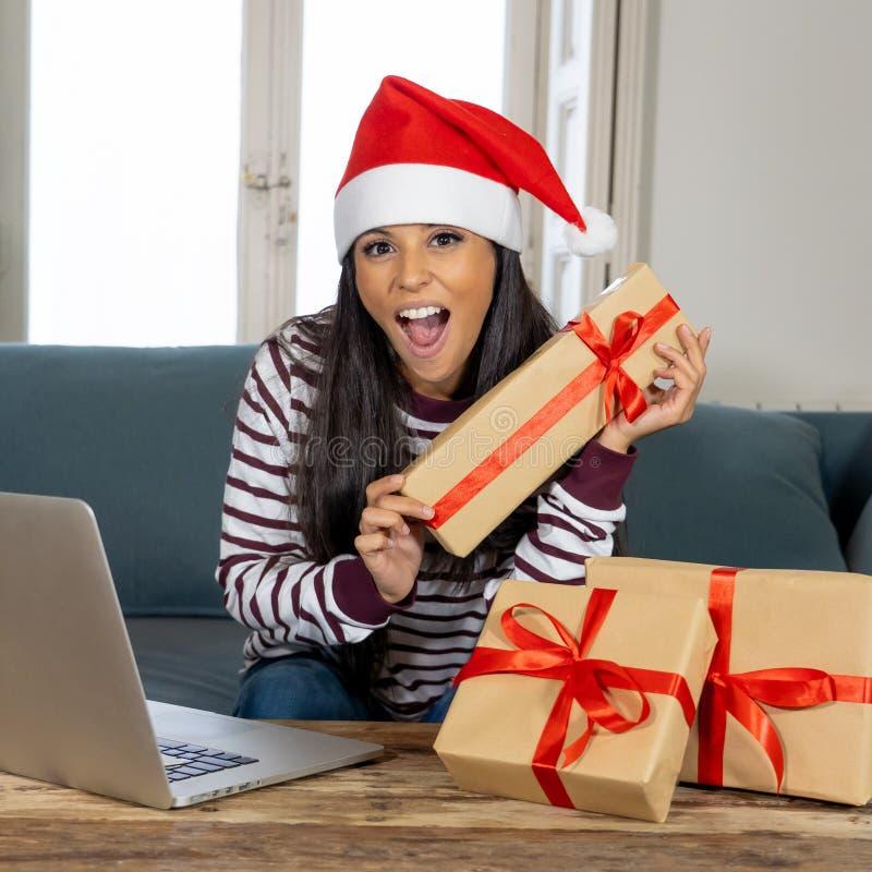 Ευτυχές ελκυστικό σε απευθείας σύνδεση να φανεί χριστουγεννιάτικων δώρων αγοράς γυναικών συγκινημένος με τα δώρα στοκ φωτογραφίες με δικαίωμα ελεύθερης χρήσης