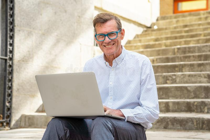 Ευτυχές ελκυστικό ώριμο άτομο που εργάζεται στο lap-top που ελέγχει τη συνεδρίαση ηλεκτρονικού ταχυδρομείου στη αστική περιοχή σκ στοκ εικόνες