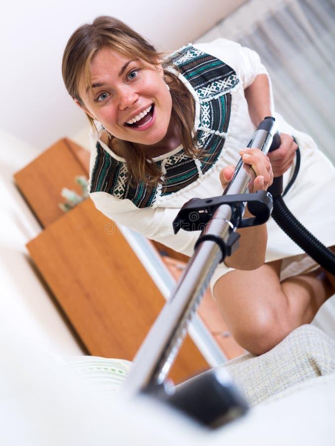 Ευτυχές ενήλικο σκουπίζοντας με ηλεκτρική σκούπα πάτωμα κοριτσιών στοκ εικόνα