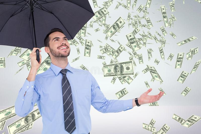 Ευτυχές επιχειρησιακό άτομο κάτω από την ομπρέλα που εξετάζει τη βροχή χρημάτων στο άσπρο κλίμα στοκ εικόνα