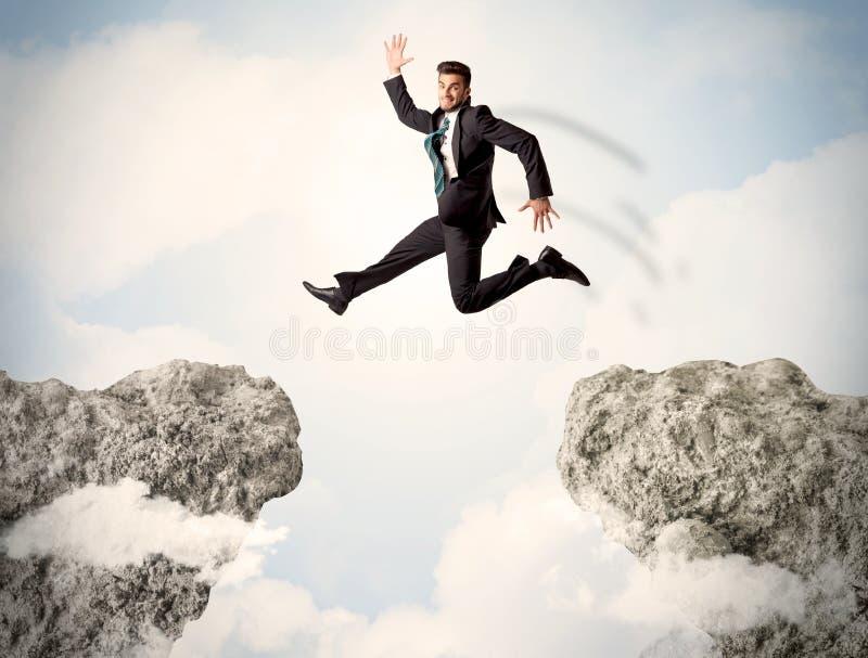Ευτυχές επιχειρησιακό άτομο που πηδά πέρα από έναν απότομο βράχο στοκ εικόνα με δικαίωμα ελεύθερης χρήσης