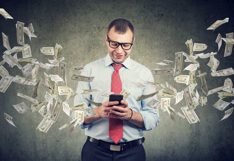 Ευτυχές επιχειρησιακό άτομο που χρησιμοποιεί το smartphone με τους λογαριασμούς δολαρίων που πετούν μακρυά από την οθόνη στοκ φωτογραφία